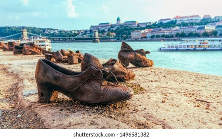 Budapest, Hungary / July 14 2019: Old metal rusty shoes on the parapet of the Danube river embankment in Budapest, Hungary. Monument to the victims of Nazi repression. Nazi terror and the Holocaust