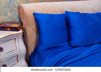 BUDAPEST, HUNGARY - JULY 21, 2018: Beautiful blue bedding on the bed with ornaments on the wall and a bedside table with a book, expensive silk on the pillows and bed sheet, royal interior