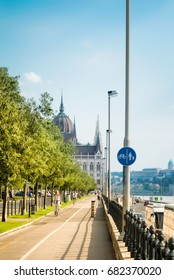 BUDAPEST, HUNGARY - JULY 24, 2016: Bike path at the Danube embankment at the center of Budapest and signs, and Parliament building at the background, Hungary.