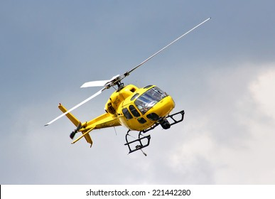 BUDAPEST, HUNGARY - JULY 26, 2014: Yellow helicopter Eurocopter AS-355N Ecureuil 2 at the sky above the Hungaroring Formula One Race Track.