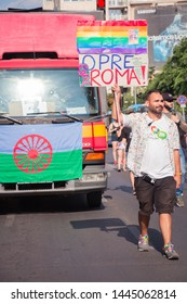 Budapest, Hungary - July 6, 2019: Man walks and holds up a board in front of a red truck that is ornamented by the Gypsy flag, during the Budapest Pride parade.
