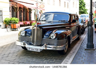 Budapest, Hungary - July 6, 2019: Old passenger vintage car on a city street. Advertising car of   St. George Residence .