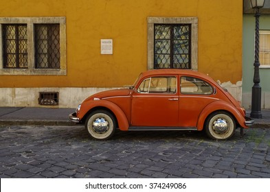 Budapest, Hungary - July 9, 2015: Orange retro economy car - Volkswagen Beetle parked on the old street of Budapest. Side view