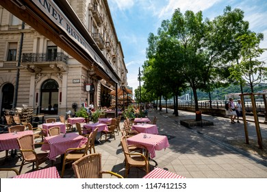 Budapest Hungary - Jun 16 2018: People walk along the chain of restaurants and coffee house at the Danube embankment in summertime.