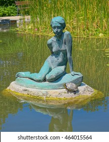 BUDAPEST, HUNGARY - JUNE 14, 2016: Bronze statue of sitting girl, created in 1932 by Imre Csikasz, located in small pond of Japanese Garden of Margaret Island in Budapest, Hungary. Selective focus.