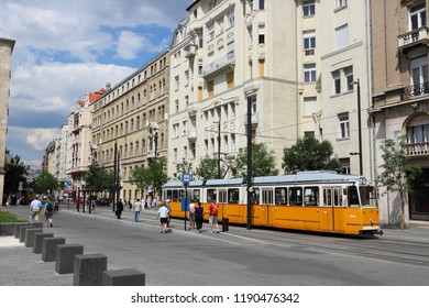 BUDAPEST, HUNGARY - JUNE 19, 2014: People ride orange tram in Budapest. It is part of BKK public transport system which serves 1.4 billion annual rides (2011).