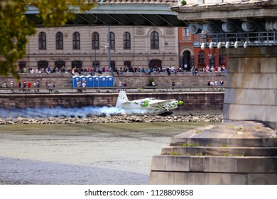 Budapest, Hungary, June 23. 2018: A Corvus Zivko Edge 540 Red Bull Air Race aircraft flies under the Chain Bridge on the Danube river, during an open for the public air show at the city of Budapest.