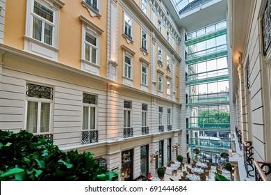 "BUDAPEST, HUNGARY - JUNE 3, 2017: Interior grand atrium inside Corinthia Hotel Budapest, known as ""Grand Hotel Budapest"" or ""Grand Hotel Royal"".  Atrium has a restaurant at ground level."