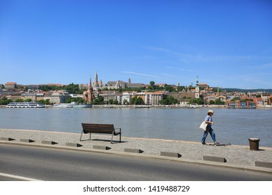 Budapest, Hungary, June 3, 2019. Cityscape on a sunny summer day a tourist walks along the embankment of the river Danube