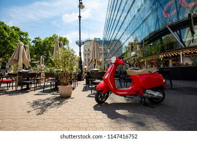Budapest, Hungary - Maj 24, 2018: People having a coffee on  Vorosmarty square in center of Budapest. The team of the restaurant is the Red Scooter.