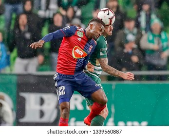 BUDAPEST, HUNGARY - MARCH 13, 2019: (l-r) Stopira battles for the ball in the air with Endre Botka during Ferencvarosi TC v MOL Vidi FC Hungarian Cup match at Groupama Arena.