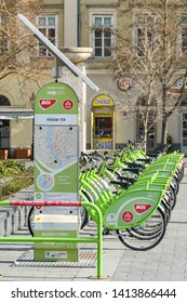 BUDAPEST, HUNGARY - MARCH 2018: Bicycles for hire in their docking stations in Budapest city centre. A city map and solar panel for power is in the foreground.