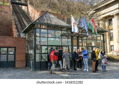 """BUDAPEST, HUNGARY - MARCH 2018: People queuing outside the ticket office of the Budapest Castle Hill Funicular railway or """"Budavári Sikló""""."""
