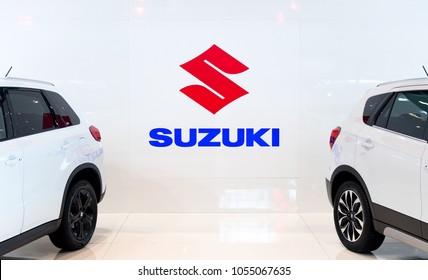 BUDAPEST, HUNGARY - MARCH 25, 2018: Suzuki logo on a white background between two Suzuki cars