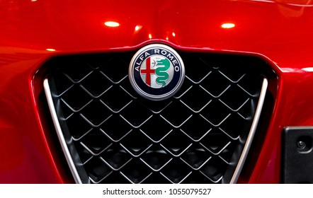 BUDAPEST, HUNGARY - MARCH 25, 2018: New Alfa Romeo logo on the front of a red Alfa Romeo Giulia sports car with the iconic front grille