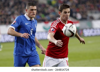 BUDAPEST, HUNGARY - MARCH 29, 2015: Hungarian Zoltan Gera (r) is followed by Greek Kyriakos Papadopoulos during Hungary vs. Greece UEFA Euro 2016 qualifier football match in Groupama Arena.