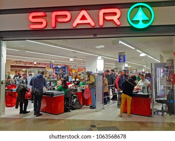 BUDAPEST, HUNGARY - MARCH 29TH 2018: The facade of a very large Spar shop with many customers paying for their groceries at the multiple registers. The name and logo are lit up. Illustrative editorial