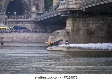 Budapest, Hungary - May 1, 2016. A Corvus Racer 540 Red Bull Air Race aircraft flies down the Chain Bridge on the Danube river, during an air show at the city of Budapest.