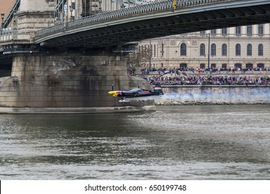 Budapest, Hungary - May 1, 2016. A Corvus Racer 540 Red Bull Air Race aircraft flies down the Chain Bridge on the Danube river, during an open for the public air show at the city of Budapest.