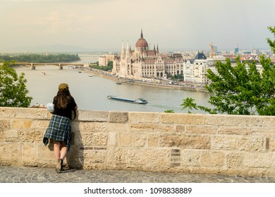 BUDAPEST, HUNGARY,- MAY 11,2018: Woman observing Hungarian Parliament from the view point on Buda bank of Danube in Budapest, Hungary.