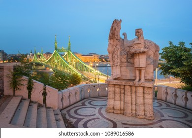 Budapest, Hungary - May 12, 2018: Statue of Stephen I at the  Gellert Hill, background shows the Liberty bridge and Danube river.