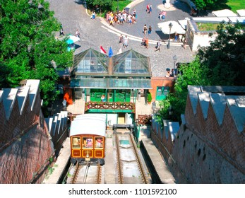 Budapest, Hungary - May 28, 2018: Tourists climb up to the Budapest Castle on the funicular railway from the Adam Clark Square and the Széchenyi Chain Bridge. Group of people below in the square.