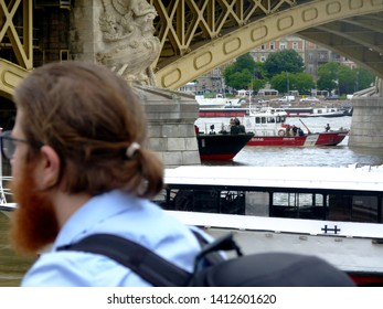 Budapest, Hungary - May 31, 2019: Photographer rushing to the location of the salvage operations on the Danube river under the yellow Margaret Bridge, the accident scene of the May 29th boat collision