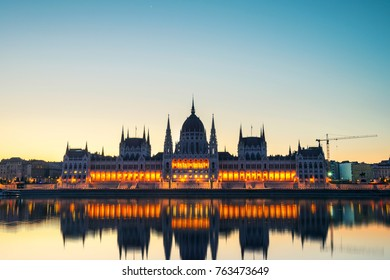 Budapest, Hungary. Morning view of illuminated Parliament building in Budapest, Hungary with motion blurred river. Very bright sky at sunrise