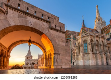 Budapest, Hungary - North gate of the Fisherman's Bastion (Halaszbastya) with the beautiful Matthias Church at golden sunrise and clear blue sky