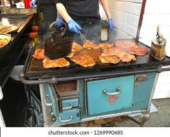 Budapest, Hungary - November 9, 2018: Christmas Market and Winter Festival at Vorösmarty Square - Pork being pressed and cooked over a coal fired Luxor grill