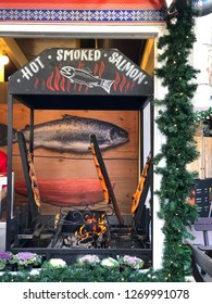 Budapest, Hungary - November 9, 2018: Christmas Market and Winter Festival at Vorösmarty Square - Salmon being smoked at a market stall