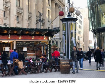 Budapest, Hungary - November 9, 2018: Tourists eating at a food stall serving smoked salmon at the Vörösmarty Square Christmas Market and Winter Festival beside an ad column promoting McDonald's