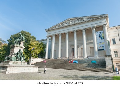 BUDAPEST, HUNGARY - OCTOBER 26, 2015: Budapest Palace with Local people sitting on the colorful bench and reading. Old Statue on the left