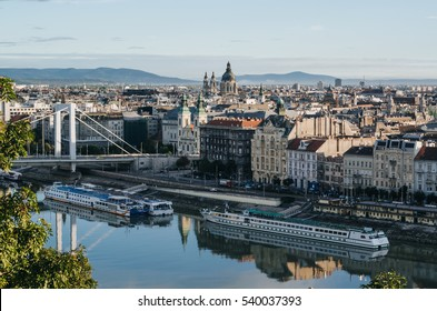 BUDAPEST, HUNGARY - SEPTEMBER 18, 2016: Two big ships moored on Danube river near Elizabeth bridge, St. Stephen's cathedral and Inner City Parish Church (Belvaros Church) in the morning.