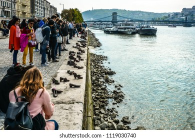 Budapest, Hungary - September 26 2017: Tourists visit and take photos at The Shoes on the Danube Bank, a memorial in Budapest, Hungary with the Chain Bridge and boats in the background