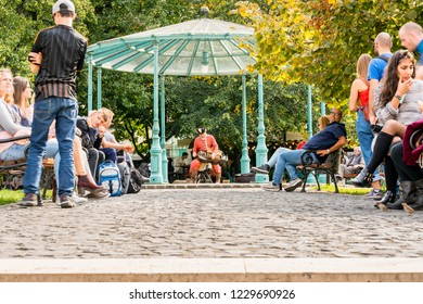 BUDAPEST, HUNGARY - SEPTEMBER 27, 2017: Low ground view of people resting in a public park. A male street performer in the middle playing traditional instrument in Budapest Hungary September 27, 2017.