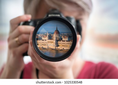 Budapest, Hungary - Young happy blonde tourist woman in grey coat and sunglasses taking photos of Budapest landmarks with Buda Castle Royal Palace, River Danube and sightseeing ship at background