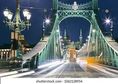 Budapest at night. Tram on old iron bridge - Szabadsag hid (Liberty bridge).