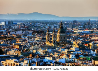 Budapest at sunset, capital city of Hungary cityscape with St. Stephen's Basilica and Ferris Wheel.