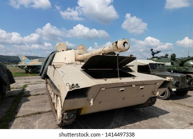 BUDAPEST/HUNGARY - 05.18, 2019: An old soviet 2S1 Gvozdika self-propelled howitzer with 122 mm gun on display at a defense show. Bright summer day with blue sky. Other armored vehicles in background.
