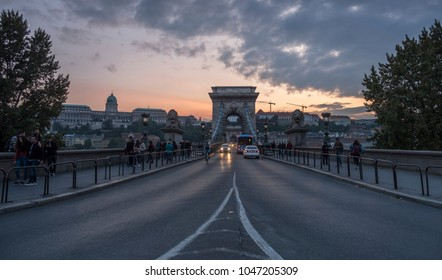 BUDAPEST/HUNGARY - 25 SEPTEMBER 2017: Low angle wide shot of traffic crossing the Chain Bridge in Budapest. Taken at dusk looking towards Budpa Castle