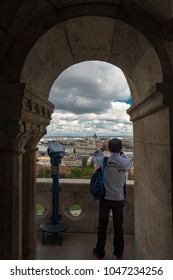 BUDAPEST/HUNGARY - 25 SEPTEMBER 2017: Tourist takes photo of Budapest Parliament as seen through arch in Matthias Church, Hungary.