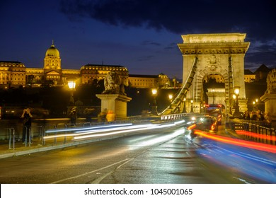 BUDAPEST/HUNGARY - 25 SEPTEMBER 2017: Twilight shot of traffic and light trails crossing the Chain Bridge in Budapest. The city lights are on and Buda Castle is in the background