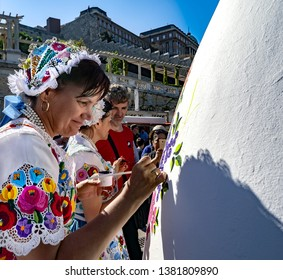 BUDAPEST,HUNGARY - April 21, 2019.: Woman dressed in traditional costumes,paint a giant Easter egg with Kalocsa folk flower motifs on the square  in front of Castle Garden Bazaar. (Varkert Bazar)