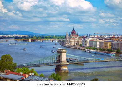 Budapest/Hungary- April 30, 2019: spring aerial view of the city with colorful old historical and modern buildings, beautiful Parliament, Danube River, bridges, Margit Island and touristic cruise boat