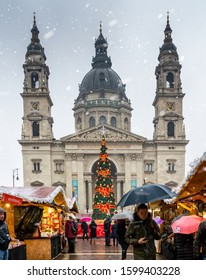 Budapest/Hungary - December 12, 2019: A busy Christmas market in front of the famous St. Stephen's Basilica in Budapest Hungary with people walking with umbrellas in the winter snow.