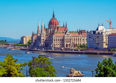 Budapest/Hungary- May 6, 2018: spring aerial view of the city with colorful old historical and modern buildings, beautiful Parliament, Danube river, bridge, touristic boats and hills on the horizon.