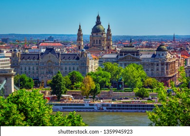 Budapest/Hungary- May 7, 2018:Aerial spring cityscape with colorful old historic buildings, St. Stephen's Basilica, Danube River, cruise touristic boat, green trees and blue sky.