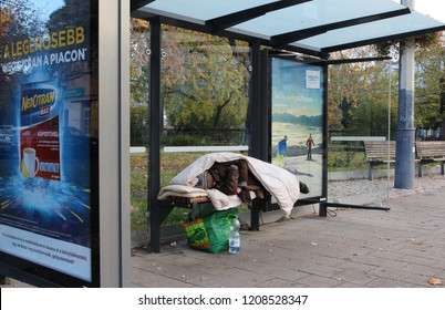 Budapest,Hungary,11.11.2017.Homeless person sleeping on a bench in a bus stop.Hungary's constitution now says sleeping on the streets is a crime.