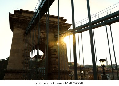 Budapest's famous Chain Bridge connecting the towns of Buda and Pest. iconic stone gate and iron chains and sun flare behind it.